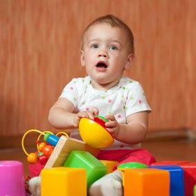 Малыш в девять месяцев играет в кубики